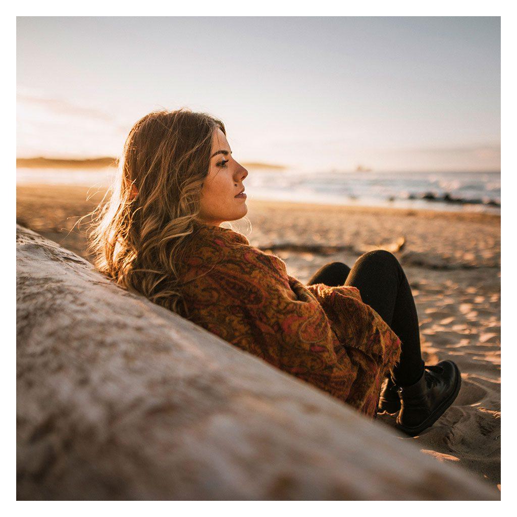 Junge Frau am Strand träumt